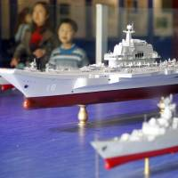 Visitors look at models of an aircraft carrier fleet, including Beijing's first aircraft carrier, the Liaoning (back), on display in Nanjing, China, on April 13. | AFP-JIJI