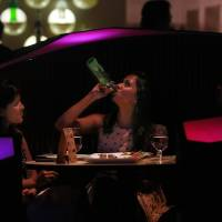 An Indian woman drinks with her friend at the blueFROG nightclub in Mumbai. | AP