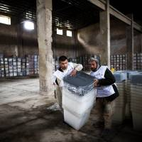 Election workers move ballot boxes at a warehouse in the northwestern city of Herat on Thursday. Afghans are set to vote Saturday in the country's third presidential election since the fall of the Taliban in 2001. | AFP-JIJI