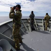 Crew members on the Australian Navy's HMAS Perth scan the Indian Ocean for debris from Malaysia Airlines Flight MH370 on Thursday. | REUTERS
