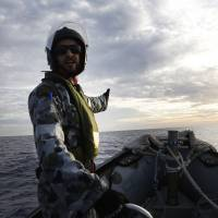 A crew member directs the coxswain on a Rigid Hull Inflatable Boat of the Australian Navy ship HMAS Perth while searching for debris from missing Malaysia Airlines Flight MH370 in the southern Indian Ocean on Monday. | AFP-JIJI