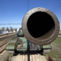 A T-62 tank is prepared for shipment back to Ukraine from the Ostryakovo railway station near Simferopol, Crimea, on Monday, as Ukrainian forces pulled out of the region following its annexation by Russia. | AP