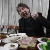 Korean food blog operator Joe McPherson samples a serving of skate with kimchi and boiled pork at a seafood store in Seoul on March 12. | AP
