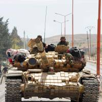 Syrian soldiers on Monday drive a tank through al-Sarkha village, in the Qalamun mountains northeast of Damascus, after wresting control of it from rebel fighters. | AFP-JIJI