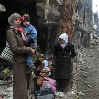 This photo, released by Syrian news agency SANA, shows residents of the besieged Yarmouk Palestinian refugee camp on the southern edge of Damascus waiting to leave on Feb. 4. | AP
