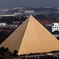 In Hunan province, a pyramid rises skyward on the corporate campus of Chinese multimillionaire Zhang Yue. He has also built himself a replica of the Palace of Versailles. | AFP-JIJI