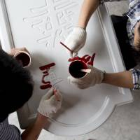 Laborers paint a sign at a movie-themed town under construction in Haikou, southeastern China, last Saturday. | BLOOMBERG