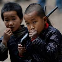 Young members of the Miao minority group carry replica guns in Biasha, China, in February. | AFP-JIJI
