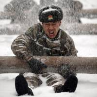 A Chinese soldier trains during heavy snowfall on Feb. 26 in Heihe, in the northeastern province of Heilongjiang. | REUTERS