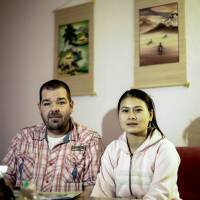 Michael Guhle and his Vietnamese wife, Thi An Nguyen, sit in their apartment in Berlin in February. | AP
