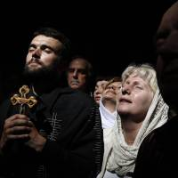 Worshippers react to a beam of sunlight filtering from the ceiling as they take part in the Christian Orthodox Holy Fire ceremony at the Church of the Holy Sepulchre in Jerusalem's Old City on Saturday. | REUTERS