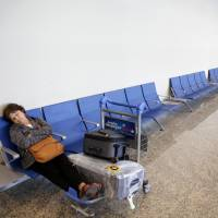 A traveler naps at Jorge Newbery airport in Buenos Aires on Thursday. | BLOOMBERG