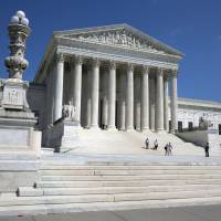 People walk on the steps of the U.S. Supreme Court in Washington on Saturday. | AP
