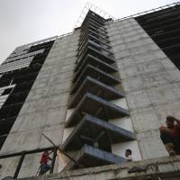 The 45-story 'Tower of David,' seen Feb. 3 from the 30th floor, was intended to be a shining new financial center in the heart of Caracas but it was abandoned in 1994 after the developer's death. Squatters in 2007 invaded the huge concrete skeleton, turning it into the highest slum in the world. It now houses 3,000 people. | REUTERS