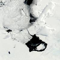 These photos taken Dec. 10 (left) and March 11 by NASA show a large iceberg separating from the Pine Island Glacier and traveling across Pine Island Bay in Antarctica. Scientists are watching the iceberg, which is bigger than the island of Guam, as it slowly moves away from the glacier (bottom right in December, upper left center in March). | AP