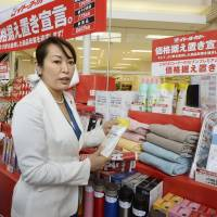 Consumer affairs minister Masako Mori picks up merchandise at an Ito-Yokado supermarket in Koto Ward, Tokyo, on Tuesday. | KYODO