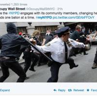This frame grab from a Twitter post by @OccupyWallStNYC shows a photo of a New York Police Department officer wielding a baton during an Occupy Wall Street rally in the city. The photo was posted as a Twitter request by the NYPD for feel-good photos of people posing with friendly police officers backfired spectacularly. | AP