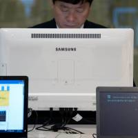 A man uses a computer at a Samsung showroom in Seoul on April 8. The arrest of a South Korean man who apparently spent days playing Internet games, allowing his 2-year-old son to starve to death, has brought the issue of online game addiction in the country into sharper focus. | AFP-JIJI