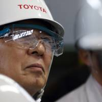 Mitsuru Kawai, senior technical executive of Toyota Motor Corp., looks at workers in the forging department at one of the company's plants in Toyota, Aichi Prefecture, in February. | BLOOMBERG