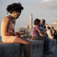 A woman uses her cellphone in Havana on March 11. A U.S. agency masterminded a 'Cuban Twitter,' a communications network designed to undermine the communist government, built with secret shell companies and financed through foreign banks. | AP