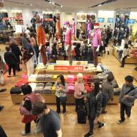 Shoppers browse through clothing at the opening of Australia's first Uniqlo store in Melbourne on Wednesday. | BLOOMBERG