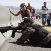 A protester aims his weapon from a bridge next to the Bureau of Land Management's camp, where seized cattle belonging to rancher Cliven Bundy were being held in Bunkerville, Nevada, on April 12. | REUTERS