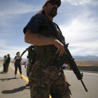 A protester carries a rifle on a bridge next to the Bureau of Land Management's base camp in Bunkerville, Nevada, on April 12. | REUTERS