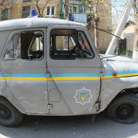 A damaged police vehicle is parked outside a military base in the southeastern Ukraine city of Mariupol on Thursday. Despite the crisis in Ukraine and Washington's sanctions against Moscow, U.S. carmakers say the Russian market is their next big frontier. | AFP-JIJI