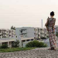 A woman holding a baby looks out over the Tama New Town residential development in western Tokyo last August. | BLOOMBERG