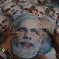 A print shop worker arranges masks depicting Narendra Modi, prime ministerial candidate for the main opposition Bharatiya Janata Party in Indian national elections, at a printing press in Ahmadabad, India, on April 12. | AP