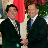 Prime Minister Shinzo Abe greets his Australian counterpart, Tony Abbott, in Tokyo on April 7. | AFP-JIJI