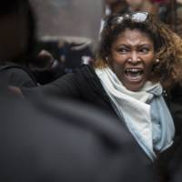 A woman shouts at police officers during the protest. | AP