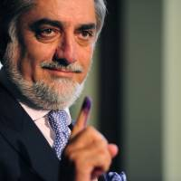 Afghan presidential candidate Abdullah Abdullah shows his inked finger while casting his vote in Kabul on April 5. | AFP-JIJI