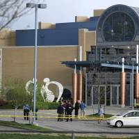 Police officers gather Sunday at the scene of a shooting at the Jewish Community Center of Greater Kansas City in Overland Park, Kansas. | REUTERS