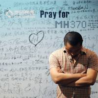 A man stands in front of a board with messages of support for passengers on Malaysia Airlines Flight MH370, as Chinese relatives of the missing held a meeting at the Metro Park Hotel in Beijing on Wednesday. The hunt for physical evidence that the jetliner crashed in the Indian Ocean has turned up nothing, despite a massive operation involving seven countries. | AFP-JIJI