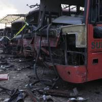 Damaged buses are seen at the scene of an explosion at a bus park in Abuja on Monday. Suspected Islamic militants struck at the heart of Nigeria with a massive rush-hour explosion that killed at least 75 at the bus station. | AP