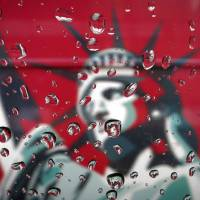 An image of the Statue of Liberty is pictured through a rain-covered taxi window in New York on Tuesday. Authorities said the same day that a special New York Police Department unit that had sparked controversy by tracking the daily lives of Muslims in an effort to detect terrorist threats has been disbanded. | REUTERS
