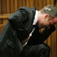 South African Paralympic track star Oscar Pistorius vomits as he listens to evidence by a pathologist during his trial at a Pretoria court Monday. | AFP-JIJI