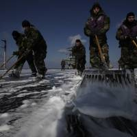 Crew members wash the flight deck of the USS Ronald Reagan in an attempt to remove radiation deposits on March 23, 2011. Sailors aboard the aircraft carrier, in the Pacific Ocean off the coast of Tohoku, had taken part in a rescue mission transporting supplies to evacuees and survivors following the Great East Japan Earthquake and tsunami. | AP