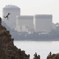 A man dives into the sea as Kansai Electric Power Co.'s Mihama nuclear power plant looms in the background in the town of Mihama, Fukui Prefecture, in July 2011. | REUTERS