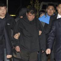 Lee Joon-seok (center), captain of the sunken Sewol ferry, arrives at a court in Mokpo, South Korea, late Friday. Investigators on Saturday arrested Lee, who is accused of abandoning the ferry that capsized last week with 476 people on board, 273 of whom remain missing. | AP