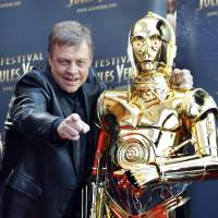 U.S. actor Mark Hamill, who played Luke Skywalker in the George Lucas Star Wars saga, poses with a figure of the character C3PO, before an April 2010 screening of 'Star Wars V: The Empire Strikes Back,' as part of the Jules Verne Festival in Paris. | AP