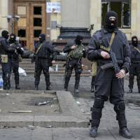 Ukrainian special forces members stand guard outside the regional administration building in Kharkiv on Tuesday. Ukraine launched an 'anti-terrorist' operation in the eastern city and about 70 'separatists' were arrested for seizing the building, Ukrainian Interior Minister Arsen Avakov said Tuesday. | REUTERS