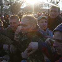 Pro-Russian activists attack the commander of a Ukrainian Army anti-terrorist operation, Gen. Vasyl Krutov (center), after he spoke outside Kramatorsk airport, in the country's east, Tuesday. | AP