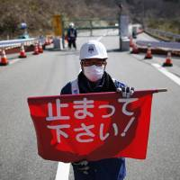 A security worker holds a flag reading 'Please Stop!' as he stand by a steel gate marking the border between the towns of Tamura and Okuma in Fukushima Prefecture on Tuesday. | REUTERS