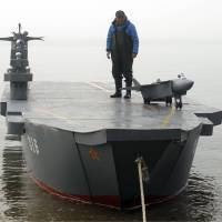 Retiree Wen Yuzhu stands on his homemade aircraft carrier in Qingdao, in east China's Shandong province, on April 2. The 80-year-old spent months building the model to fulfill his grandson's wishes. | AP
