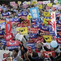 Protesters at a Tokyo park in November 2012 stage a rally against the deployment of the U.S. Marine Corps' MV-22 Osprey in Okinawa. On Friday, the U.S. Defense Department released a draft assessment of the environmental impact on Guam of the planned transfer of marines from Okinawa. | AP