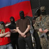Masked pro-Russian gunmen stand at City Hall during negotiations about the release of foreign military observers being held by Ponomarev's group in Slovyansk, eastern Ukraine, on Sunday. | AP
