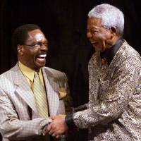 Former South African President Nelson Mandela shakes hands with former U.S. boxer Rubin 'Hurricane' Carter during the inaugural World Reconciliation Day celebrations in Melbourne, Australia, on Sept. 9, 2000. | AFP-JIJI