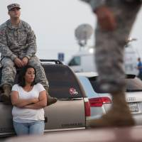 Spc. Timothy Hamlin and his wife, Lucy Hamlin, wait for permission to re-enter the military base at Fort Hood, Texas, where they live, following a shooting at the site Wednesday that left four people dead and injured 14 others. | AP